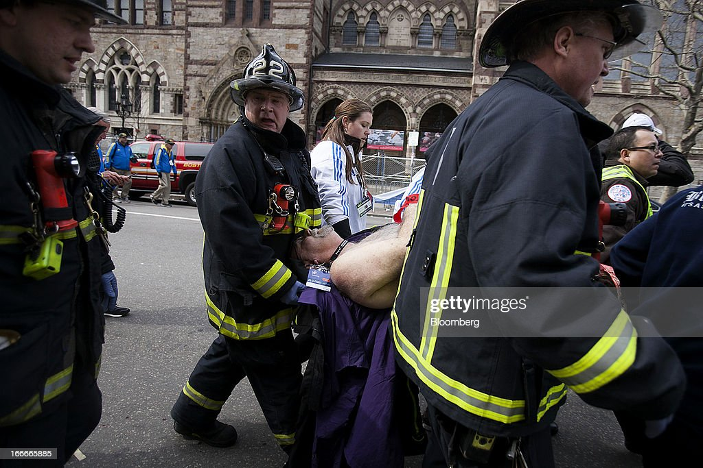 Firemen carry an injured person where two explosions occurred along the final stretch of the Boston Marathon on Boylston Street in Boston, Massachusetts, U.S., on Monday, April 15, 2013. Two powerful explosions rocked the finish line area of the Boston Marathon near Copley Square and police said many people were injured. Photographer: Kelvin Ma/Bloomberg via Getty Images