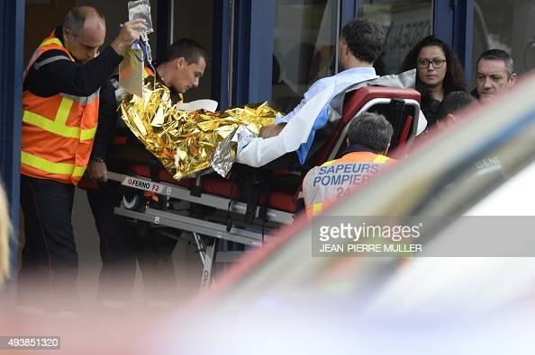Firemen carry on a stretcher a man injured in a coach accident on October 23 2015 in Puisseguin near Libourne southwestern France At least 42 people...