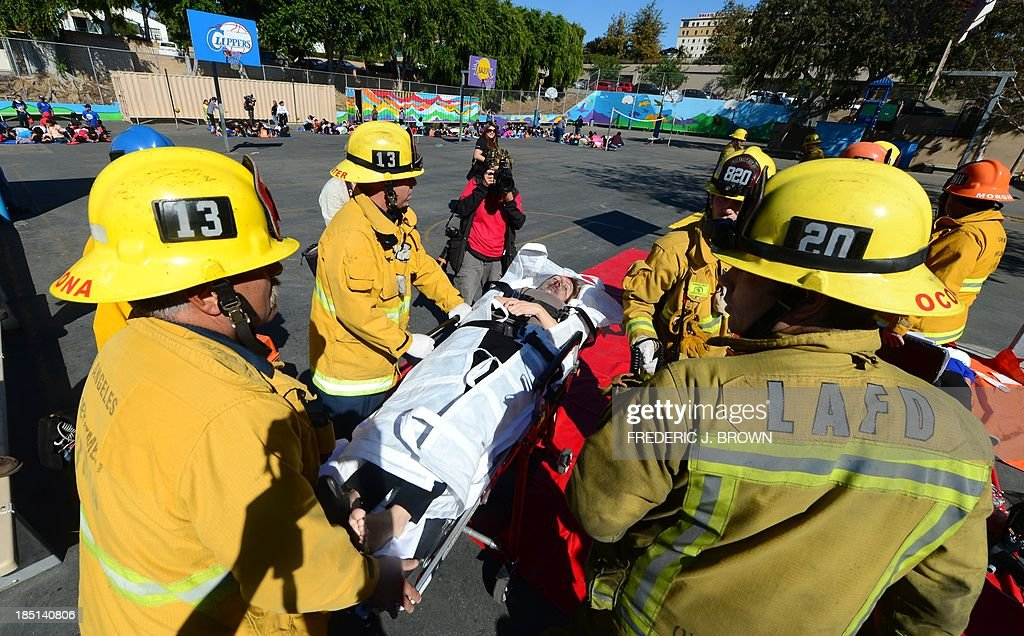 Firemen carry on a stretcher a woman with make-believe injuries during an earthquake drill at Rosemont Elementary School in Los Angeles on October 17, 2013. Millions of people across California were expected to 'drop, cover and hold on' in the earthquake drills staged across the state today in preparation for the 'Big One' expected to hit someday. AFP PHOTO/Frederic J. BROWN