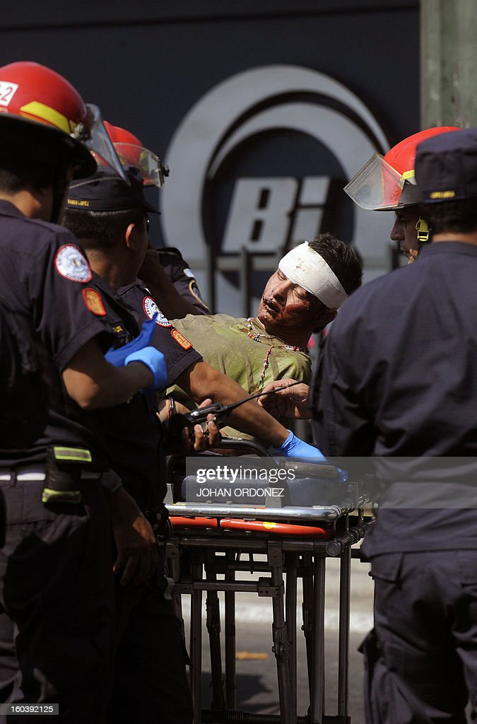 Firemen carry on a trolley a robbery suspect injured during clashes with the police in Guatemala City on January 30, 2013. The Guatemalan police chased three offenders following a car robbery, which ended in clashes that left two of them dead and one injured. Guatemala is one of the most violent countries in Latin America, with an average of 16 deaths per day. AFP PHOTO/Johan ORDONEZ