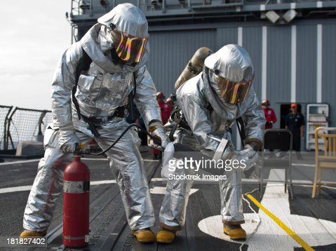 Firemen confirm a simulated fire is extinguished on the flight deck of USS Chosin.