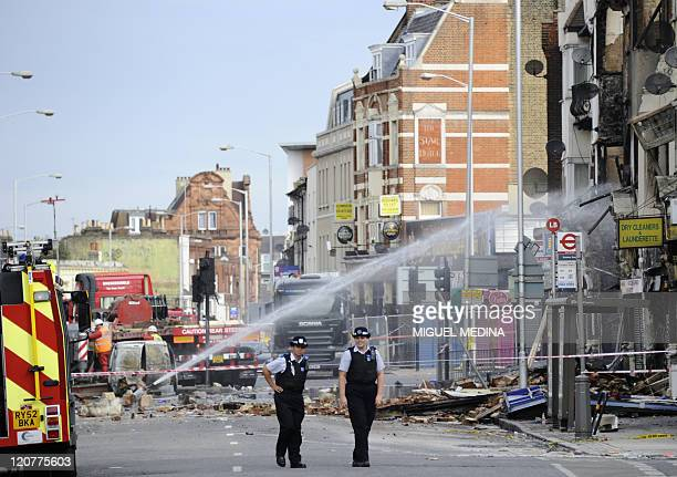 Firemen continue to douse the charred reamins of properties and businesses on London road in Croydon south of London on August 10 following riots in...