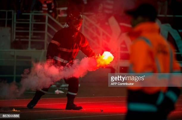A firemen controls smoke flares during the CAF Champions League quarterfinal match between Morocco's Wydad Athletic Club and South Africa's Mamelodi...