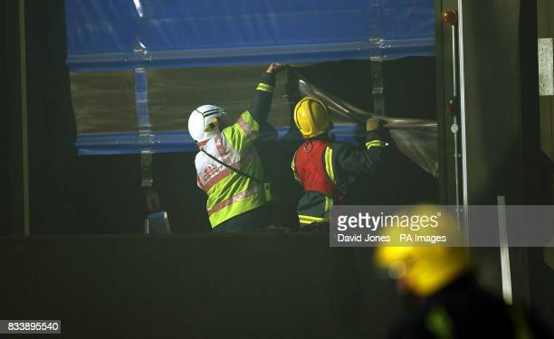 Firemen cut through a door at the scene of a fire where a colleague was killed and another three are missing today at a warehouse on an industrial...