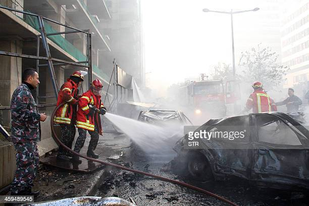 Firemen douse a burning car following a huge blast that rocked central Beirut on December 27 killing an adviser to former antiSyria coalition prime...