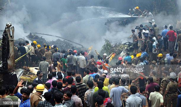 Firemen douse the smoldering remains of the aircraft that crashed on May 22 2010 in Mangalore An Air India Express Boeing 737800 series aircraft...