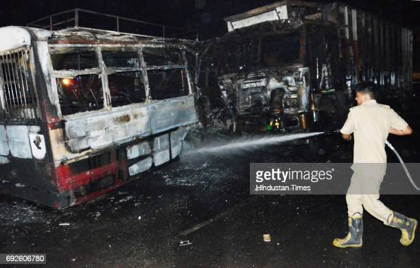 Firemen dousing the fire on bus after the collision with truck near the Bareilly bypass on June 5 2017 in Bareilly India Twentytwo people have been...