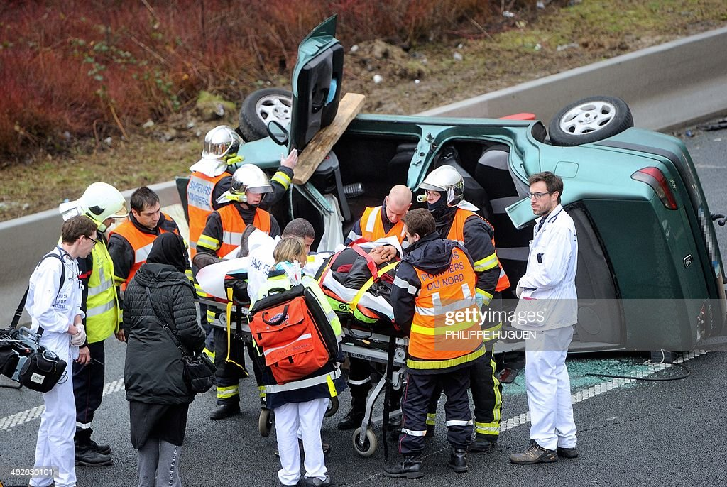 Firemen evacuate a man on a stretcher following a car crash, on January 2014 on Roubaix's ringroad.