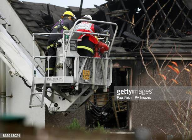 Firemen examine the remains of the terrace house in Omagh where five children along with their parents where killed in a house fire