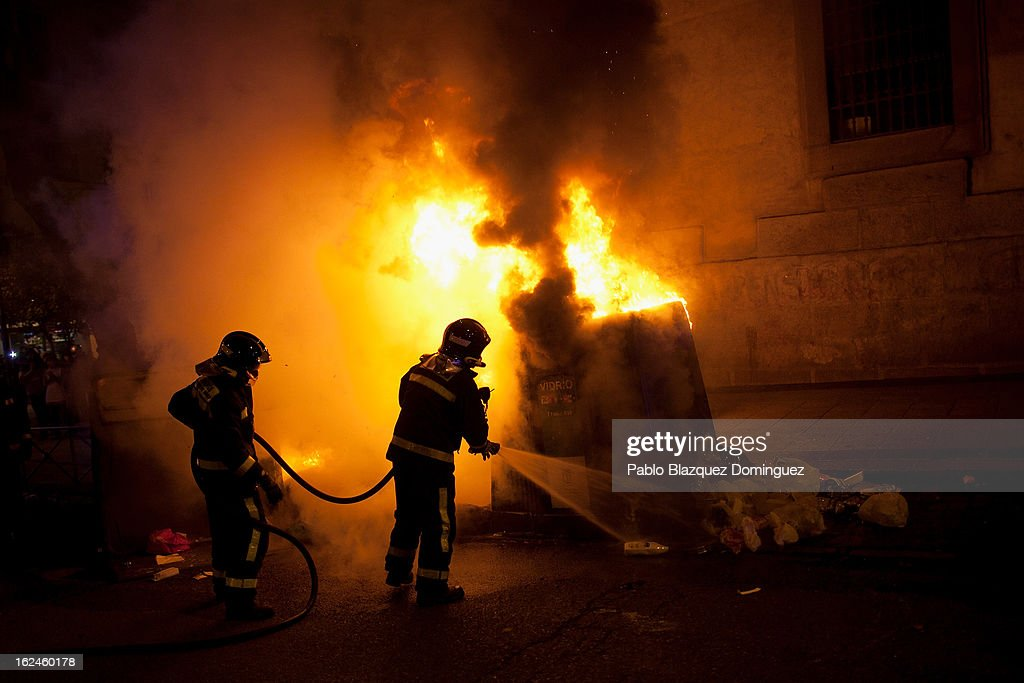 Firemen extinguish a bin on fire during riot of protesters with riot police after a march that gathered thousands of people on February 23, 2013 in Madrid, Spain. Public health workers, civil servants and disaffected citizens converged on central Madrid to protest against the austerity measures of Prime Minister Mariano Rajoy.