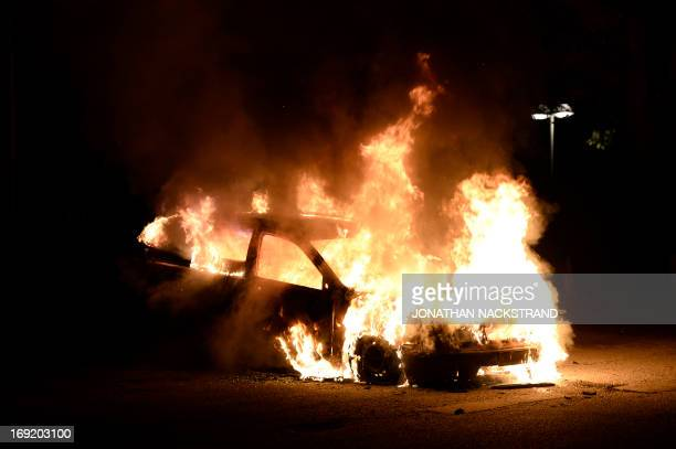 Firemen extinguish a burning car in Kista after youths rioted in few differant suburbs around Stockholm on May 21 2013 Youths in the immigrantheavy...
