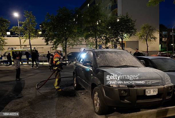 Firemen extinguish a burning car in the Stockholm suburb of Tensta after youths rioted in few different suburbs around Stockholm and Sweden on May 24...