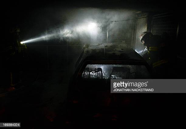 Firemen extinguish a burning car parked in an indoor garage in the Stockholm suburb of Tureberg after youths rioted in several different suburbs for...
