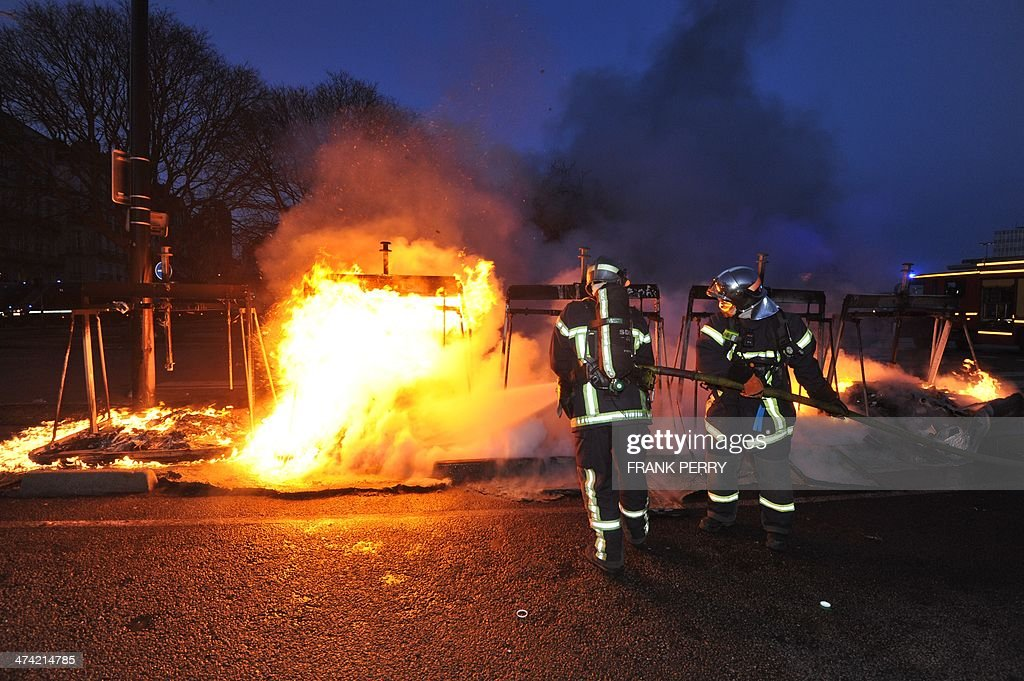 Firemen extinguish a fire after a demonstration against the project to build an international airport in the French western city of Notre-Dame-des-Landes, on February 22, 2014, in Nantes, western France,. The disputed project, signed in 2010, has been put on hold and will likely be postponed beyond the scheduled opening planned for 2017. The planned airport north of Nantes, which is scheduled to replace the city's current airport in 2017, is a pet project of Prime Minister Jean-Marc Ayrault, who was the city's mayor from 1989 to 2013. AFP PHOTO / FRANK PERRY