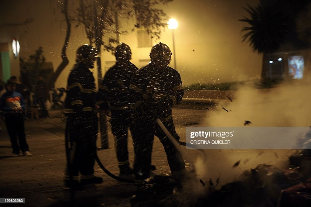 Firemen extinguish a pile of uncollected rubbish set on fire by neighbors in a street of Jerez de la Frontera on November 21, 2012. Rubbish collectors have been on strike in the municipality of Jerez de la Frontera since November 5, 2012 to protest against the austerity cuts imposed by the town hall. AFP PHOTO/ CRISTINA QUICLER