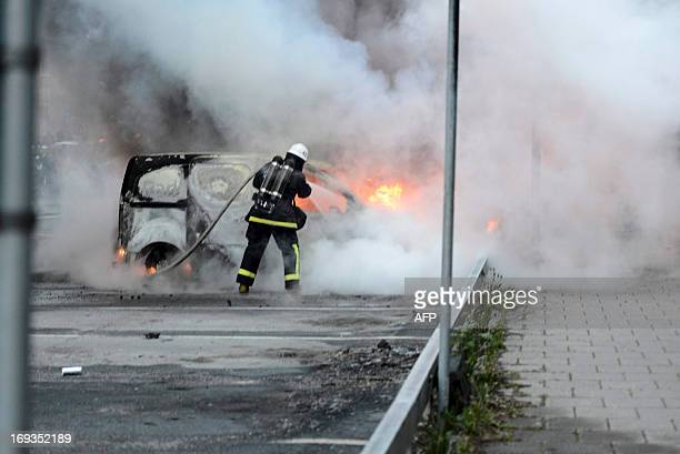 Firemen extinguish burning cars in the Stockholm suburb of Rinkeby after youths rioted in several different suburbs around Stockholm Sweden for a...