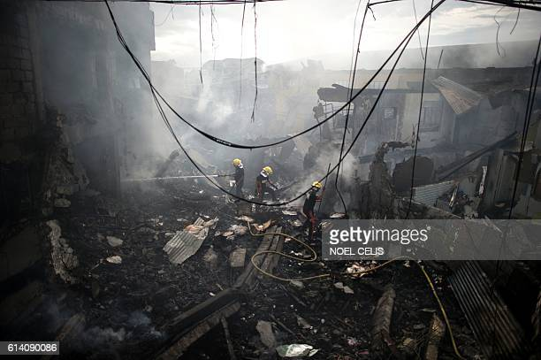 TOPSHOT Firemen extinguish the fire at a fireworks shop in Bocaue Bulacan north of Manila on October 12 2016 A fire that ripped through a group of...