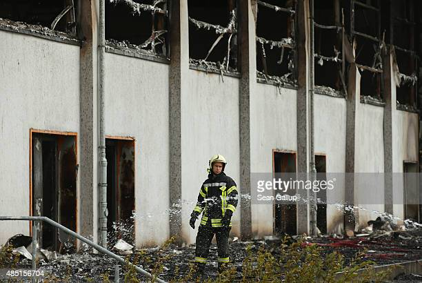 Firemen extinguish the last embers from a fire that struck a sports hall that was intended to house refugees and migrants applying for aslyum in...