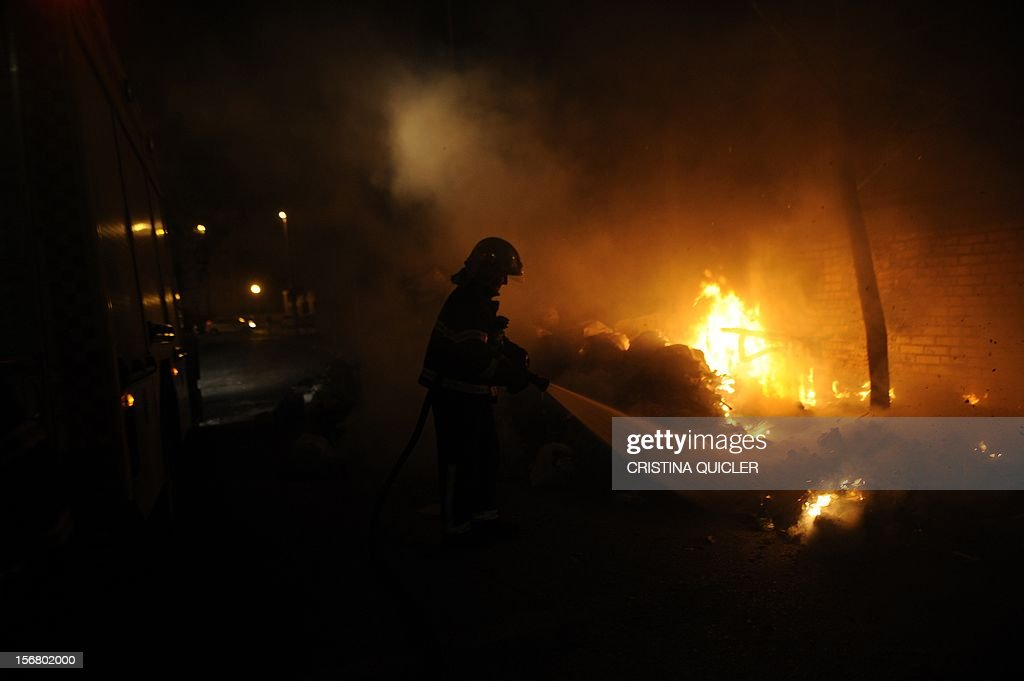 A firemen extinguishes a pile of uncollected rubbish set on fire by neighbors in a street of Jerez de la Frontera on November 21, 2012. Rubbish collectors have been on strike in the municipality of Jerez de la Frontera since November 5, 2012 to protest against the austerity cuts imposed by the town hall. AFP PHOTO/ CRISTINA QUICLER
