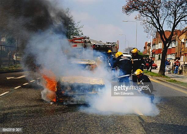 Firemen extinguishing blazing car on urban road, England