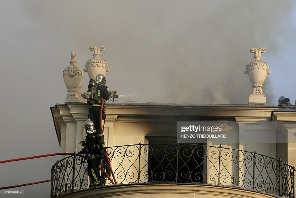 Firemen fight a blaze at the 17 century Hotel Lambert on July 10, 2013 in Paris. Hotel Lambert, by the architect Louis Le Vau located at the tip of the Ile Saint-Louis in Paris, was purchased in 2007 by the brother of the Emir of Qatar and currently being restore. AFP PHOTO / KENZO TRIBOUILLARD