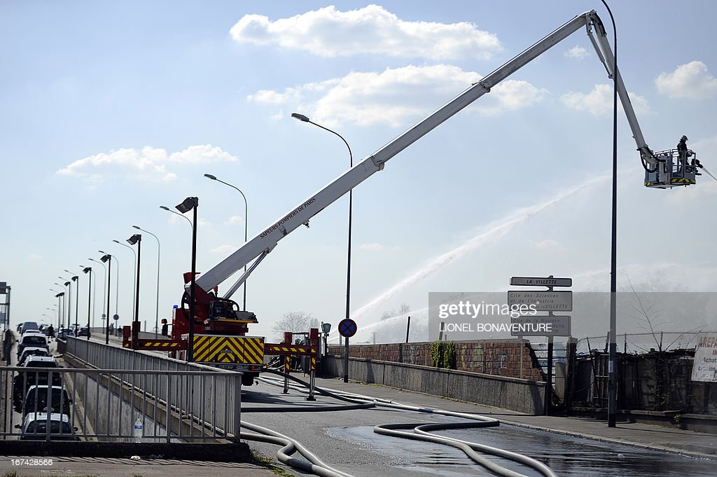 Firemen fight a fire that caught in a factory on April 25, 2013 in the Paris' suburb of Bobigny. Some 250 people from the Roma community were evacuated as the fire spread in their camp. AFP PHOTO / LIONEL BONAVENTURE