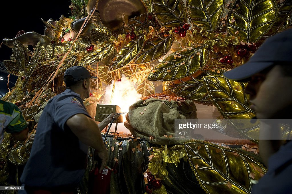 Firemen fight a principle of fire in a float of Mancha Verde samba school, during the first night of Carnival parades at Sao Paulo on February 09, 2013. AFP PHOTO / Nelson ALMEIDA