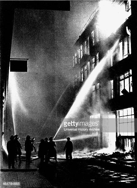 Firemen fighting a blazing City warehouse after a German air raid during the London Blitz 1940