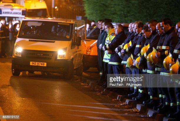 Firemen form a guard of honour as the seven bodies of the family who died in a house fire in Omagh are removed from the building in two white vans