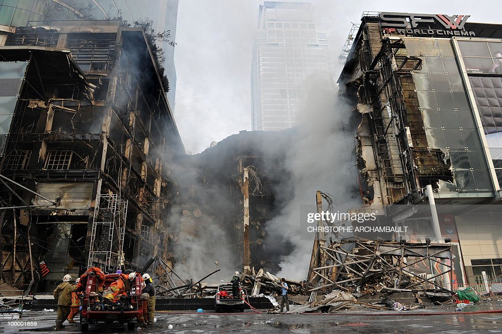 Firemen gather at Thailand's biggest shopping mall - Central World - as it keeps burning after it was set ablaze the day before following an army assault on an anti-government protest site, in downtown Bangkok on May 20, 2010. Plumes of smoke hung overhead and gunfire crackled as Bangkok emerged from an curfew aimed at quelling mayhem unleashed by enraged anti-government protesters targeted in an army offensive. AFP PHOTO/Christophe ARCHAMBAULT