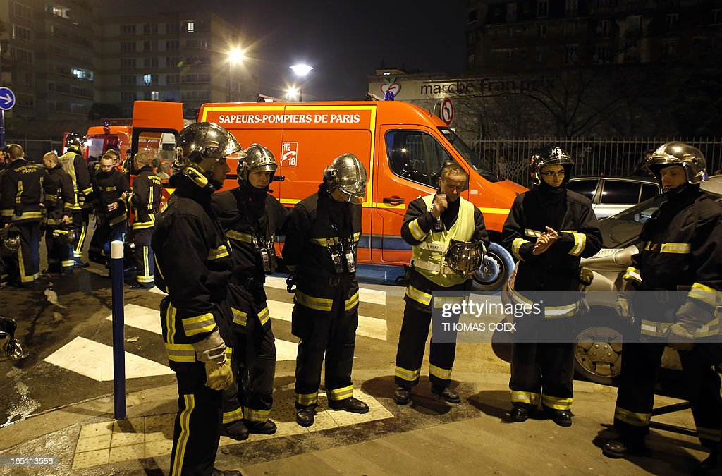 Firemen gather at the location of a building that was gutted by fire in Aubervilliers, a suburb of Paris, on March 30, 2013. Two people were killed and five others seriously injured in the fire.