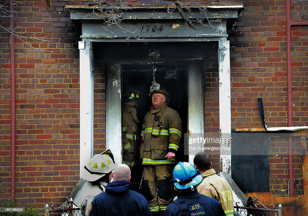 Firemen gather on the stoop in the aftermath of a fire that destroyed a rowhouse at 1704 S Street, southeast, where bodies were discovered, on February, 05, 2013 in Washington, DC.
