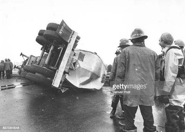 Firemen gaze at overturned tanker truck A tanker trailer carrying 4000 gallons of caustic soda overturned on the ramp from eastbound Interstate 70 to...