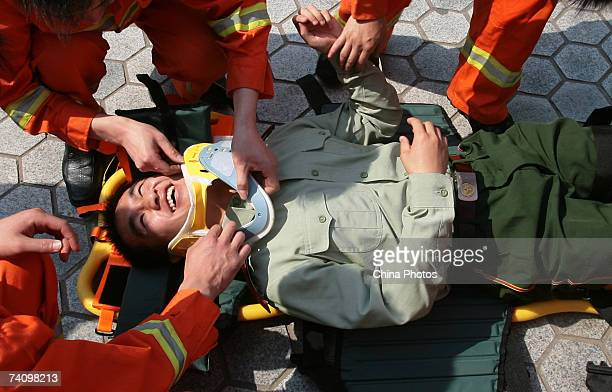 Firemen give first aid to a simulated patient during a drill to mark the World Red Cross Day on May 8 2007 in Nanjing of Jiangsu Province China...