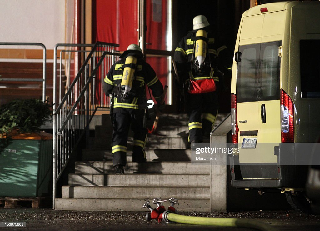 Firemen go into a Caritas employment facility for the handicapped, in which 14 people died in a fire on November 26, 2012 in Titisee-Neustadt, Germany. The fire was reportedly caused by an explosion at the facility, where approximately 120 people with disabilities are employed in light manufacturing.