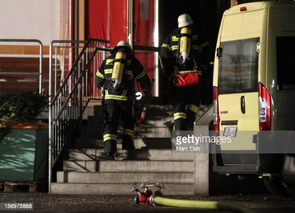 Firemen go into a Caritas employment facility for the handicapped in which 14 people died in a fire on November 26 2012 in TitiseeNeustadt Germany...