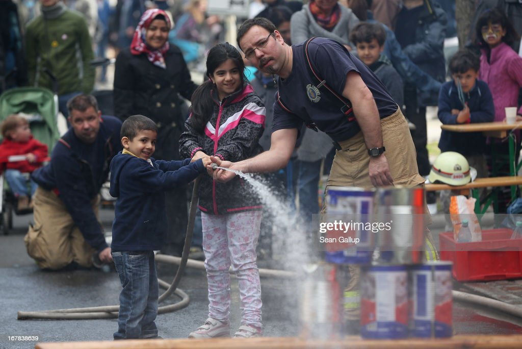 Firemen help children to aim a water hose at stacked cans at the MyFest street food and music fest in immigrant-heavy Kreuzberg district on May Day on May 1, 2013 in Berlin, Germany. May Day, the international day of labour, is a national holiday in Germany and observed with gatherings by labour unions and political parties. In some cities, including Hamburg and Berlin, the day often ends with violent clahes between police and mostly left-wing demonstrators.