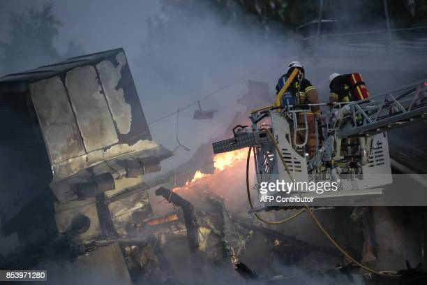 TOPSHOT Firemen in an aerial bucket try to extinguish a fire which began in the night in a mosque in Orebro west of Stockholm on September 26 2017...