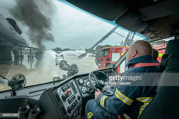 Firemen in cab of fire engine at airport training facility