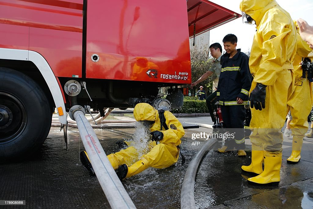 Firemen in protective suits gather near the site of an ammonia leak at a cold storage unit in Baoshan district of Shanghai on August 31, 2013. An ammonia leak from a cold storage unit at a food company in China's commercial hub of Shanghai killed 15 people on August 31 and sickened dozens, the city government said. CHINA