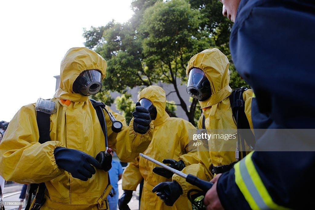 Firemen in protective suits gather near the site of an ammonia leak at a cold storage unit in Baoshan district of Shanghai on August 31, 2013. An ammonia leak from a cold storage unit at a food company in China's commercial hub of Shanghai killed 15 people on August 31 and sickened dozens, the city government said. CHINA OUT AFP PHOTO