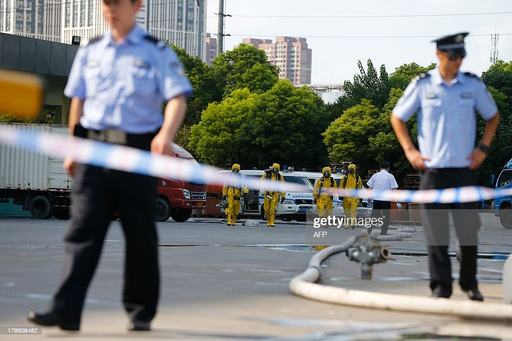 Firemen (C yellow) in protective suits walk at the site of an ammonia leak at a cold storage unit in Baoshan district of Shanghai on August 31, 2013. An ammonia leak from a cold storage unit at a food company in China's commercial hub of Shanghai killed 15 people on August 31 and sickened dozens, the city government said. CHINA