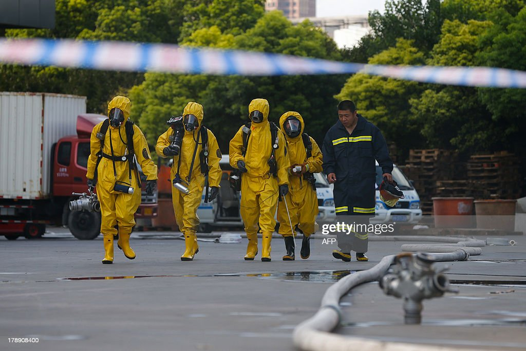 Firemen in protective suits walk near a cold storage unit following an ammonia leak in Baoshan district of Shanghai on August 31, 2013. An ammonia leak from a cold storage unit at a food company in China's commercial hub of Shanghai killed 15 people on August 31 and sickened dozens, the city government said. CHINA
