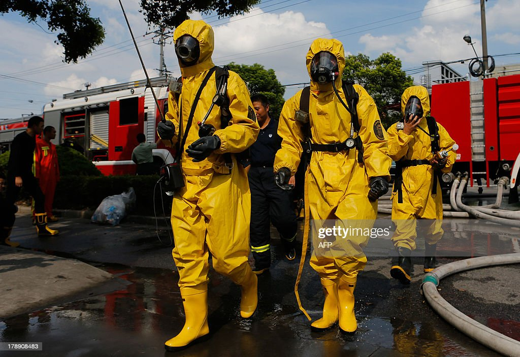 Firemen in protective suits walk near the site of an ammonia leak at a cold storage unit in Baoshan district of Shanghai on August 31, 2013. An ammonia leak from a cold storage unit at a food company in China's commercial hub of Shanghai killed 15 people on August 31 and sickened dozens, the city government said. CHINA