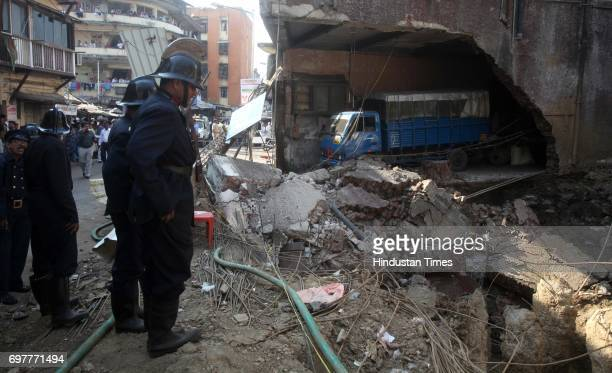 Firemen inspect the wall of centuryold vacant building Yah Allah that came crashing down at Kamathipura on Monday afternoon No one was injured when...