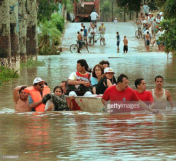 Firemen lead a boat with residents of Palmares Brazil down a flooded street 03 August 2000 after the Una river overflowed from heavy rains in the...