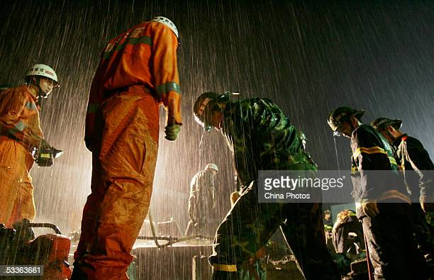 Firemen lift a piece of block in rain to excavate a victim buried in rubbles after a basement of Tiandi Store collapsed at Nanqiao Village in wee...