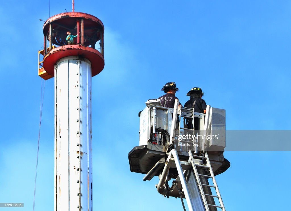 Firemen look on as workers disassemble the Astrotower in Coney Island on July 4, 2013 in the borough of Brooklyn in New York City. Officials decided to close Luna Park and sections of the boardwalk while workers take down the amusement tower which was seen precariously swaying two days ago.