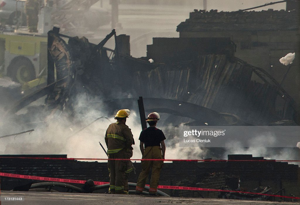 Firemen looked at the smouldering remains of a derailed train Three people have now been declared dead and dozens remain missing after a train...