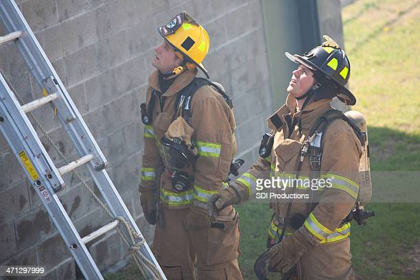 Firemen Looking Up To Top of Wall